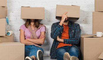 Couple with boxes on their heads surrounded by boxes